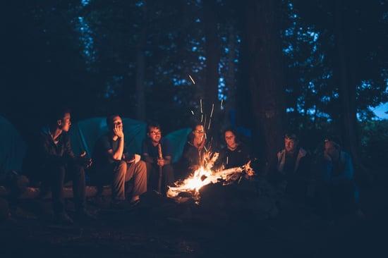 gruppo amici riuniti intorno al fuoco