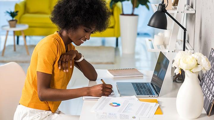 donna con maglia gialla e laptop
